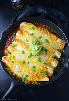 Easy and delicious chicken enchiladas recipe made in a single cast iron skillet for easy cleanup. Topped with a handful of Mexican cheese and guacamole.