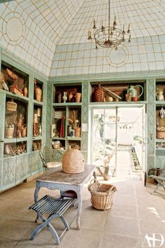 Artist Fernand Renard painted the trompe l'œil shelving displays on the greenhouse cabinetry.