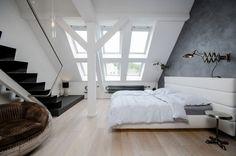 chambre adulte mansardée avec un grand lit et parquet flottant