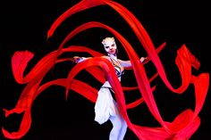 Dancer with red ribbons in black light show (UV light). Crystal Light Show/Anta Agni