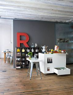 deep gray walls with matching shelf, stark white island, corrugated ceilings and a perfectly-worn wood floor