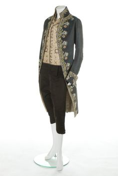3-piece court suit, c. 1790. Black and blue striped cannelé silk, elaborately embroidered in floss silks with stylised blooms, appliquéd with lace and muslin lilies, spangled with large mica sequins, ivory silk lining; waistcoat: ivory silk, embroidered with large aureoles with sequin and purl wire centres; pair of breeches: black silk taffeta.