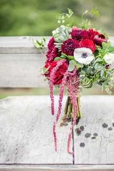 beautiful bouquet was a mix of burgundy dahlias and peonies, red roses, dark pink cascading amaranthus, white anemones, succulents, and greenery. | Photo by Kreate Photography + Design