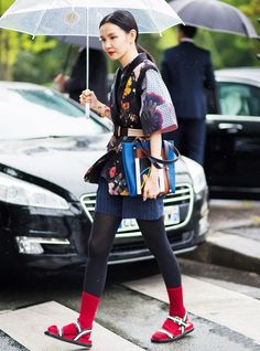 A floral top is worn with a belted vest, pinstripe shorts, tights, red socks, and flats sandals