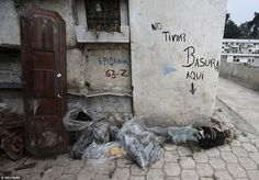 The mummified body of a woman lies on the floor and next to a wall with the writing 'no littering here' - still intact, she cannot be bagged like other decomposed remains.