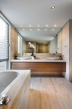 Full wall mirror, white & timber vanity; neutral materials expand the visual look of the smaller space