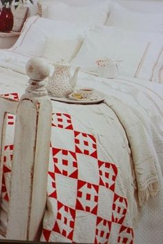 Guest bedroom with red and white quilt, white sheets, and white wood bedstead