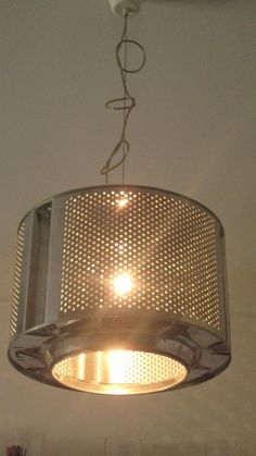 Washing machine drum repurposed as a pendant lamp