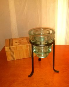 Took an antique Whitall Tatum Co. No. 1 aqua glass insulator and turned into a tea light candle holder by adding a simple black metal stand. The glass
