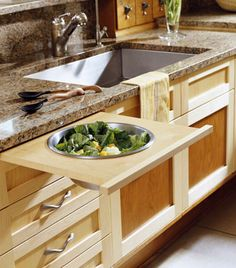 Pullout bowls, cutting boards and racks next to the sink create a workspace without needing to move from the sink, then slide back in, completely hidden in an upscale kitchen. Homedesignsoftware.com