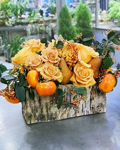 roses, persimmon, and pears in a rustic container