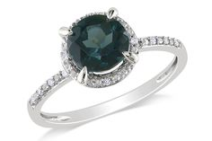This incredible ring puts all the charm and style right at your fingertips literally! A round cut london blue topaz is majestically circled and flanked by round cut white diamonds, and set in a band of pristine white gold.