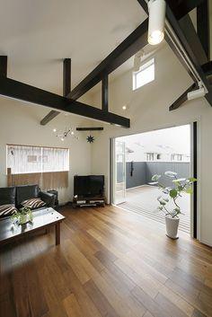 ワイドバルコニーに隣接したリビング空間は無垢床材仕上げです。勾配天井に表しの梁は、構造梁で塗装仕上げにて仕上げています。