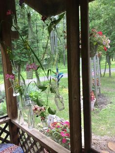 I hung flea market bud vases to make a curtain of flower clippings from my gardens.