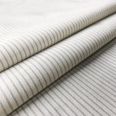 Curtain linings don't have to be plain! Lining Stripe Sage is a neutral cotton lining fabric that features multiple delicate-coloured pinstripes. With an extremely timeless yet simple design, it is perfect for adding a luxury finishing touch to any curtains or blinds. It will ensure that your curtains look as beautiful from outside your windows as they do from inside. This 100% cotton fabric is suitable for curtains, blinds and cushions. Curtain Lining Fabric, Lined Curtains, Curtains With Blinds, Striped Fabrics, Upholstered Furniture, Simple Designs, Sage, Neutral, Delicate