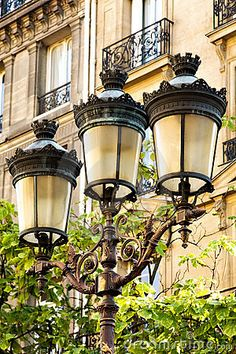 Photo about A Street Lamp in Paris holding three old-fashioned lamps, with apartment balconies in the background. Lantern Post, Lantern Lamp, Street Lamp, Paris Street, Oil Lamp Centerpiece, Centerpiece Wedding, Barcelona Street, Shabby Chic Lamps, Photos Of Eyes