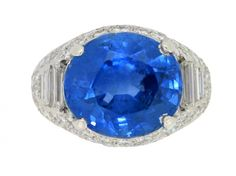 Vintage Sapphire and Diamond Cluster Ring by Oscar Heyman Brothers. Set with a cushion shape old cut natural unenhanced Ceylon sapphire in an open back claw setting with an approximate weight of 11.45 carats, flanked by six rectangular channel set tapered baguette cut diamonds in open back half rubover settings with a combined weight of 0.80 carats, encircled by a cluster of seventy four round brilliant cut diamonds in open back grain settings with a combined weight of 1.80 carats, ca…