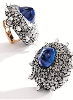Pair of Blackened Silver, 18 Karat Gold, Sapphire and Diamond Earclips, JAR, Paris - Photo Sotheby's    Centered by two sugarloaf cabochon sapphires weighing approximately 18.29 and 17.21 carats within sculptural surrounds set with numerous round diamonds of near colorless, gray and black hues, the reverse set with additional round diamonds, unsigned, with workshop marks.