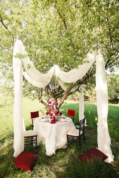 The wedding couple table, spread the sheets of fabric out to make more of a tent feel and put a rug under table and add lots of pillows!