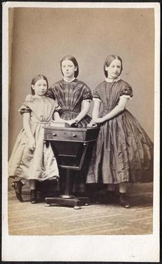 Three mid 19th century sisters (or friends) wearing dresses with short sleeves and shorter hem length, characteristic of children