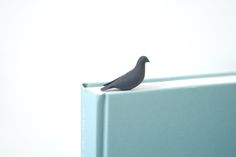 Black 3D printed bird sitting as a book mark on top of a grey bluish book on a white background