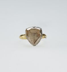 Charles I's ring. A gold ring set with large shield-shaped diamond carved with intaglio Prince of Wales's feathers and CP monogram. [Charles I when Prince of Wales] The heart shaped back enamelled with quiver of arrows and bow on dark blue ground.