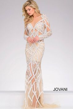 Long sleeve nude and white fitted gown features crystal embellishments, a sheer neckline, an open back and a hidden zipper in the back.