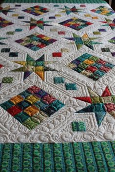 Beautiful quilting on a scrappy quilt with white background