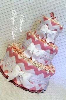 """This Baby Diaper Cake in a Baby Pink Chevron theme would be created with 50 Luvs sz 1 diapers, 3 handmade flannel burp cloths in a baby pink chevron print. Attached to a 12"""" cake plate, then wrapped with burp cloths, and layered with white ribbon & a """"It's a Girl!"""" grosgrain ribbon. Tier tops decorated with pinks & white mixed paper shred, wrapped in protective cellophane and tied with mixed curling ribbons, a party favor & gift tag. #timelesstreasure"""