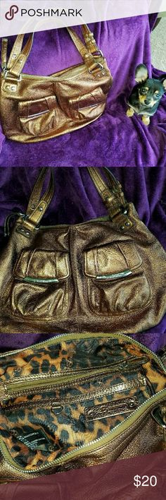 """Vintage B.Makowsky Genuine Leather Bag Slightly used & still in fantastic condition. Color is a metallic bronze.  The quality of this bag is so impressive. All buckle hardware is made of a heavier quality material. 100% Genuine leather body/trim & 100% polyester lining.  12.5"""" deep & nearly 17"""" wide. All zippers & pockets are still fully functioning.  As you can seen we are a dog friendly home & the nosy pup is not included. This is not a smoke-free home but all items are kept in an enclosed…"""