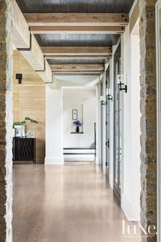 Exposed hand-hewn beams with metal brackets and dark stained-oak ceilings contrast with clean white walls in the hallway.