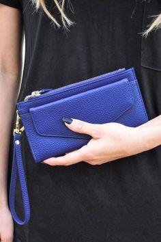 """The perfect grab-and-go wallet! The new """"Classic Navy Zippered Wallet"""" is a great color pop for this season. Easy to fit the necessities, this wallet is a must for quick errands around town. * 7. 75"""" Long, 0. 5"""" Wide, 4"""" Tall * Two zipper compartments with snap button between, opens to card and bill pockets * Front pocket with magnetic snap closure * Wrist band, faux-leather"""