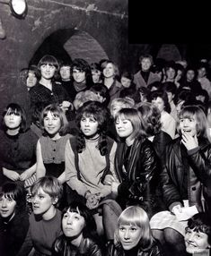 """Fans watching The Beatles at the Cavern Club, Liverpool, early 1960s. """"They'd keep their rollers in and jeans for the first groups. Then when it got near the time for the Beatles to come on, if there was a gang of four, say, they would go off in turns to the Ladies with their little cases to get changed and made up. When the Beatles came on they looked as if they'd just arrived.""""  (Maureen Cox)"""