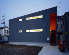 グレーの外壁にオレンジ色のエントランスが印象的な外観