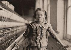 """Whitnel, Carolina del Nord. Una dei filatori della Cotton Mill Whitnel. La bambina era alta 130 cm. Lavorò in fabbrica per un anno a volte anche di notte per 48 centesimi al giorno.  Quando le fu chiesto quanti anni avesse, lei esitò, poi disse: """"Io non ricordo"""", poi ha aggiunse confidenzialmente, """"Non sono abbastanza grande per lavorare, ma fa lo stesso."""" Su 50 dipendenti, c'erano dieci bambini circa come lei. Foto di Lewis Hine."""