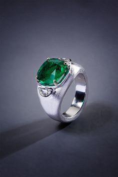 Hans Brumann Jewls. 18 karat white gold + yellow gold ring with cushion cut Columbian emerald 5.08 carats and two diamonds 0.81 carat