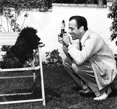 Humphrey Bogart takes a picture of his dog.
