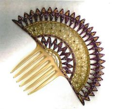 This comb is an Art Deco extravaganza. It is a celluloid comb made at the comb factories in Oyonnax, c. 1920. A small geometric pattern builds to diamond-shaped purple rhinestones to flowers to purple and orange arches at the top. Unbelievably, this is unsigned.