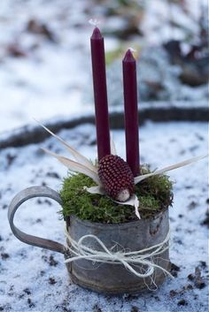 simple floral design, old tin cup with moss, candles.  Could be used for individual placesettings