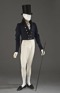 A Dandy tailored men's outfit with cream pantaloons that are a bit more fitted. Paired with white socks and a navy jacket.