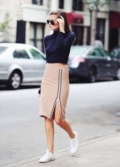Danielle Bernstein of Who What Wear dressed in a camel pencil skirt with slit and navy turtleneck cropped sweater with sneakers