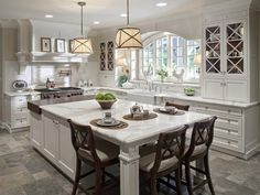 Kitchen - white cabinets with island table, linen storage drawers and display cabinet