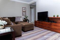 Sala de estar com tapete listrado, sofá marrom, móvel de tv em madeira, quadros na parede. Sala decorada, decoração. Repaginada na decoração sala de estar e jantar do apto