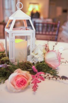 Maybe something like this... if my taste is bigger than my budget!  Lantern Style Centerpiece with moss and flower arrangement