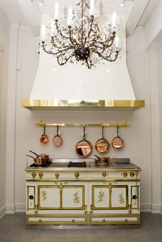 A beautiful white and gold La Cornue, copper cookware and crystal chandelier