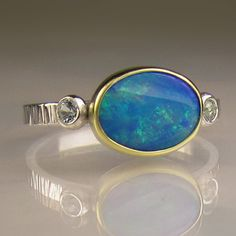 """Boulder Opal: Rather than being formed entirely of silica like the other types, boulder opals consist of seams and patches of silica that have formed within a """"host"""" or """"parent"""" rock, often ironstone which is found especially in Queensland, Australia. Depending on the location, the host rock type can vary but the resulting finished gem is a mixture of the precious opal material plus the rock it is embedded in."""