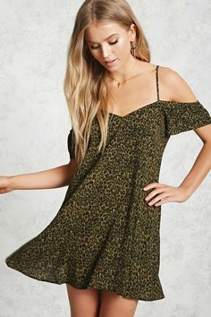 A woven dress featuring an allover leopard print, an open-shoulder design with adjustable cami straps, elasticized short sleeves, a V-neck, mini cut, and a swing silhouette.