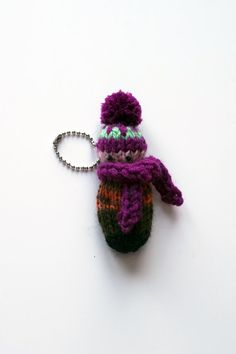 """Meet """"the little introverts""""! I knit them using woolen and acrylic yarn in a smoke free home. They are not talkative, but have their own personality and attitude. One of them could be your friend. Each doll is stuffed with sintepon, eyes are embroidered.  This little boy is wearing a brown melange sweater, beautiful purple hat with a green pattern and a big scarf. Scarf can be detachable. He is only 3,5x9,5 cm (1,4x3,7 in) in size. You can play with him or use the doll like a keychain…"""