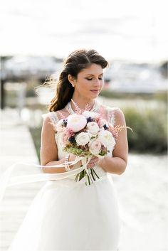 bridal portraits on the dock pink rose flower bouquet The Big Fake Wedding | The Rice Mill Charleston SC Wedding - Anchor & Veil Photography | Charlotte, NC Wedding Photographers