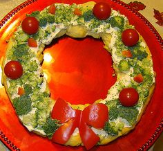 Six in the Suburbs: Christmas Crescent Roll Wreath Appetizer-2 tubes (8 ounces each) refrigerated crescent rolls  1 package (8 ounces) cream cheese, softened  1/2 cup sour cream 1 teaspoon dill weed 1/8 teaspoon garlic powder  1 1/2 cups chopped fresh broccoli florets  1 cup finely chopped celery  1/4 cup chopped sweet red pepper + sliced red pepper for bow  5 or 6 large cherry tomatoes